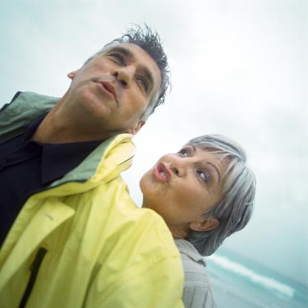 Mature couple making faces on beach, portrait LANG_EVOIMAGES