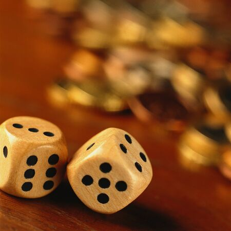 Dice in front of blurred pile of coins