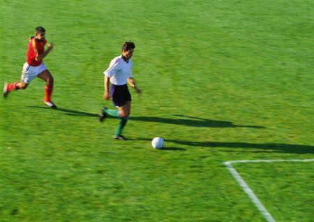 Zwei Fußballspieler, die für Ball laufen