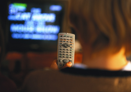 Young boy with remote in hand watching TV, rear view, close up
