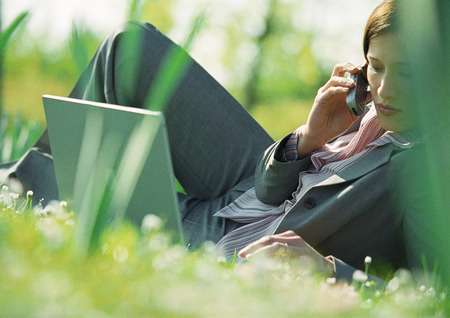 Businesswoman lying on grass with laptop and cell phone LANG_EVOIMAGES
