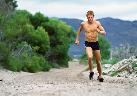 overcoming adversity: Man in shorts running along Mountain trail