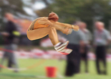 Female long jumper in mid-air, blurred motion