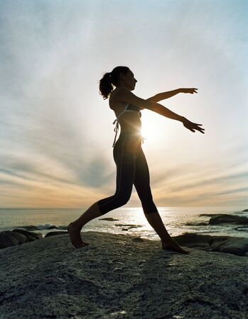Woman performing tai chi on beach, silhouette LANG_EVOIMAGES
