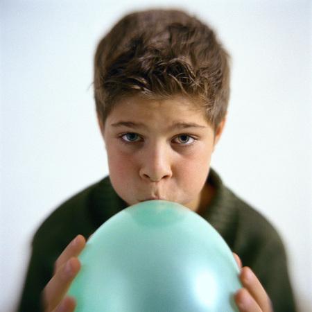 Boy blowing up balloon, portrait