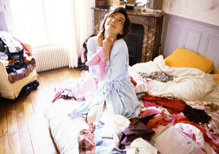Woman kneeling on bed among clothes, looking up