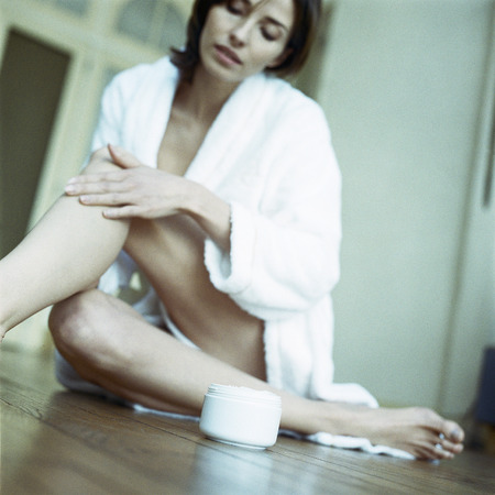 Woman sitting on floor, moisturizing legs, low angle view LANG_EVOIMAGES