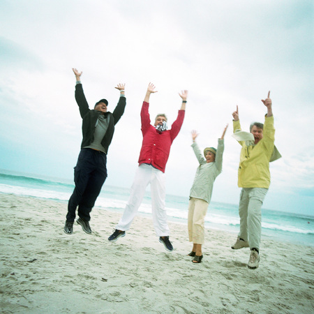 Mature group on beach, jumping in air, looking into camera LANG_EVOIMAGES