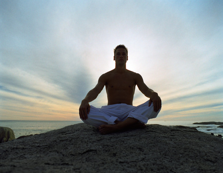 Man sitting indian style on rock, backlit, full length, sky and sea in background
