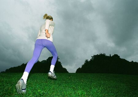 overcoming adversity: Woman running on grass, rear view, full length, low angle view, silhouette of trees in background LANG_EVOIMAGES