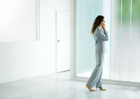 Businesswoman standing near window, using cell phone