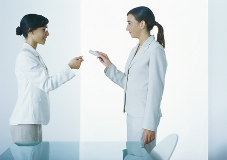 Woman handing second woman business card, side view