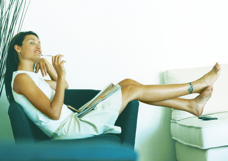 Woman sitting sideways on armchair, full length LANG_EVOIMAGES