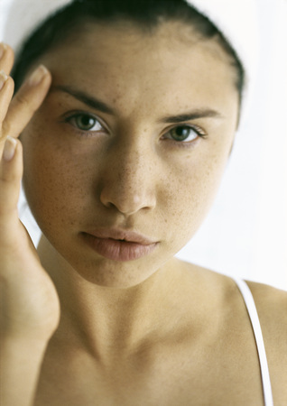 Young woman touching face with finger, close-up LANG_EVOIMAGES