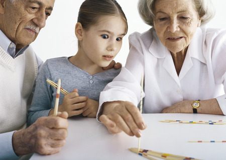 Grandparents and girl sitting at table playing pick up sticks
