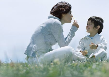 Woman and son sitting on grass, woman smelling flower