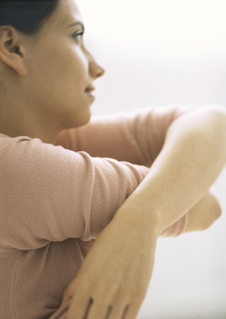 Woman taking shirt off, side view, close-up