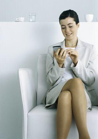 Businesswoman sitting, using electronic organizer LANG_EVOIMAGES