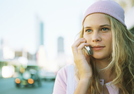 Teenage girl using cell phone in city LANG_EVOIMAGES
