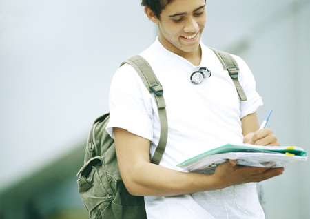 higher intelligence: Male student standing and writing on folder