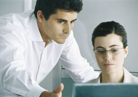 Woman working at computer, male colleague leaning over shoulder, gesturing to screen