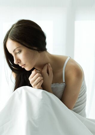 Young woman sitting up in bed, curled up