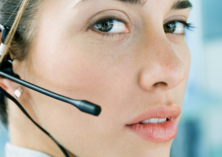 hear business call: Woman wearing headset, close-up LANG_EVOIMAGES