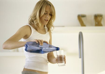 Woman pouring water into glass in kitchen