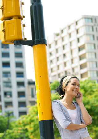 Young woman leaning against traffic-light post, talking on cell phone