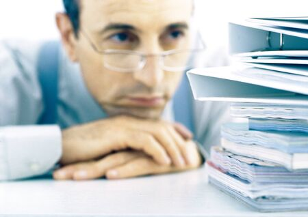 Man resting head on hands, looking at stack of files LANG_EVOIMAGES