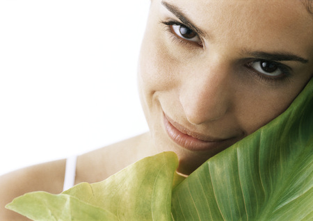 Woman tilting head against green leaf, smiling at camera, close-up LANG_EVOIMAGES