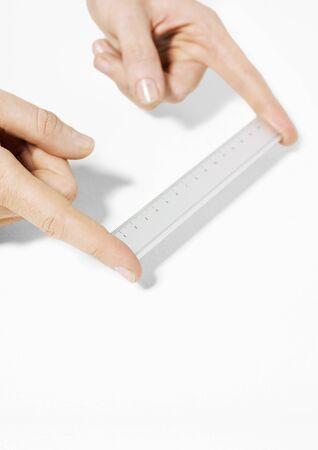 centimetres: Fingers holding ruler