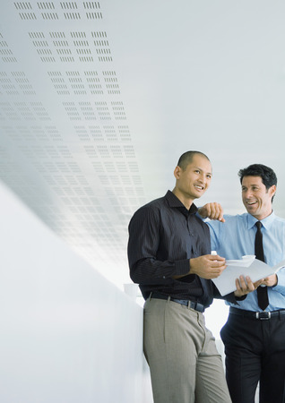 Two businessmen chatting, one holding document