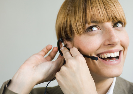 Woman smiling and putting on headset LANG_EVOIMAGES