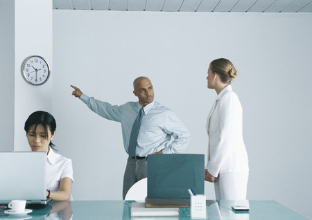 Boss pointing at clock and looking sternly at employee LANG_EVOIMAGES