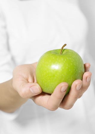 Womans hand holding out apple LANG_EVOIMAGES