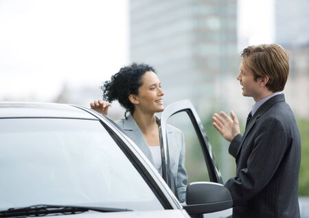 Businessman speaking to woman as she gets into car LANG_EVOIMAGES
