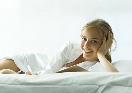 Young woman lounging on bed LANG_EVOIMAGES