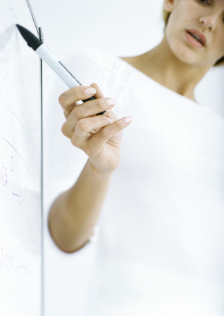 Woman pointing to board with pen, partial view