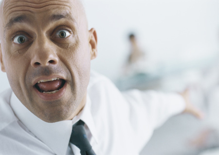 Businessman with eyebrows raised and mouth open pointing into background, close-up LANG_EVOIMAGES