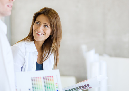 Interior decorator with color swatches smiling at colleague