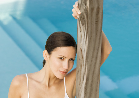 beauties: Woman standing by pool, leaning against wooden pole