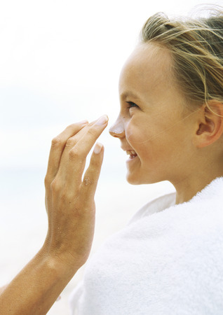 Little girl wrapped in towel having sunscreen rubbed into nose by mother