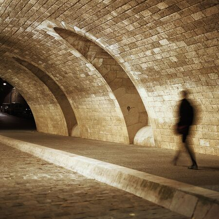 lugubrious: Person walking through tunnel at night LANG_EVOIMAGES
