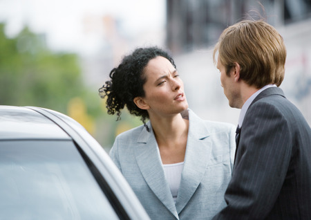 Businesswoman and man speaking next to car LANG_EVOIMAGES