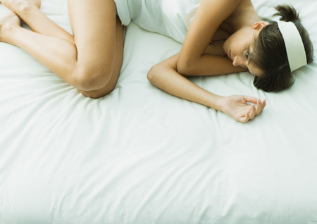 Young woman lying on bed with eyes open