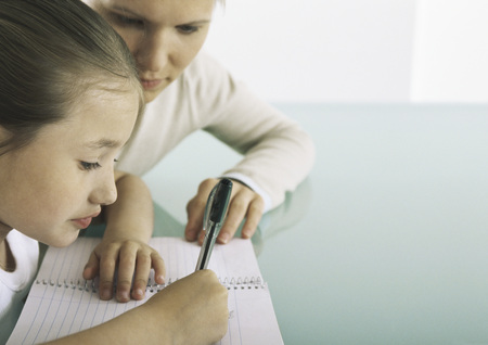 teaches: Girl sitting at table writing in notebook, woman at her side LANG_EVOIMAGES