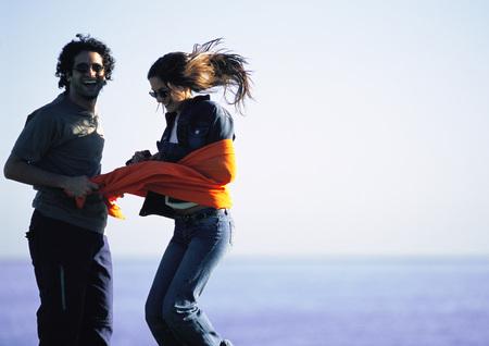 Man laughing, restraining teenage girl with orange cloth