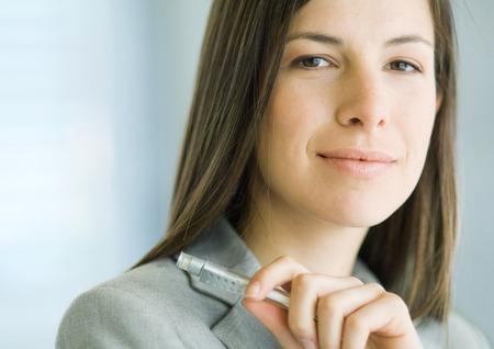 Businesswoman holding pen, close-up, portrait