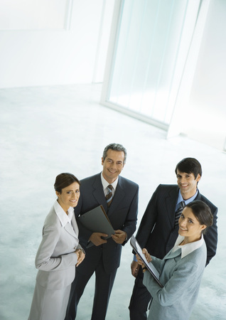 Four businesspeople standing in group, holding files